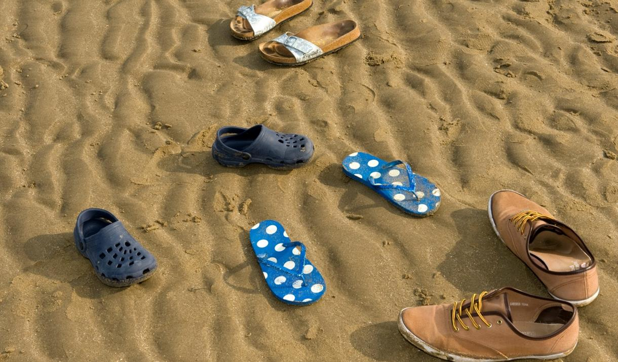 Assortment of shoes on beach