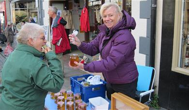 Image shows customer sampling honey at a stall at the Conwy Honey Fair