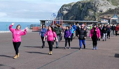 Image shows people walking on Llandudno Promenade